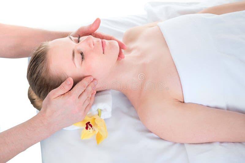 Massage de visage Plan rapproch? de jeune femme atteignant le traitement de massage de station thermale le salon de station therm images libres de droits