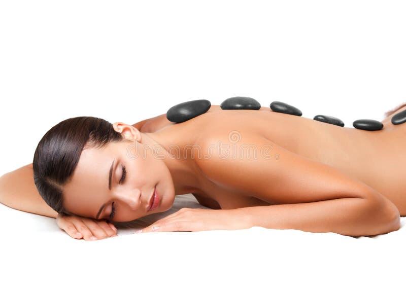 Massage en pierre. Belle femme obtenant à station thermale le massage chaud de pierres. S image libre de droits
