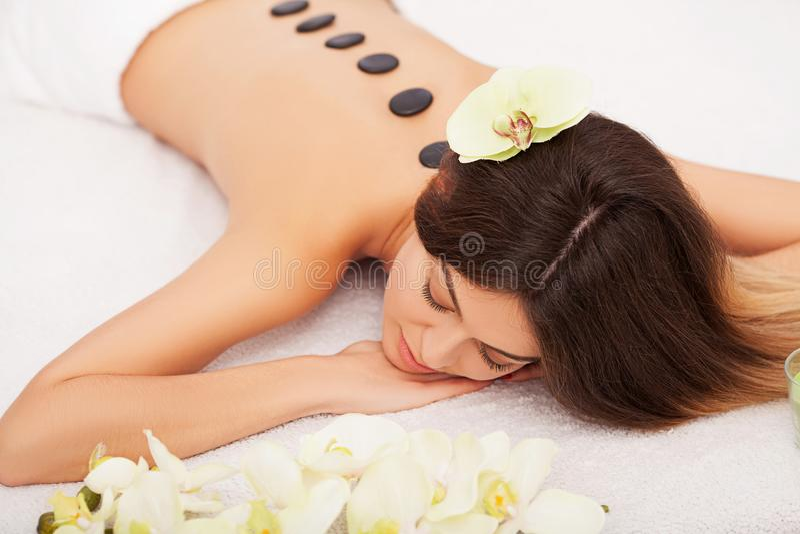 Massage en pierre de station thermale Belle femme obtenant à station thermale les pierres chaudes Massag photographie stock libre de droits