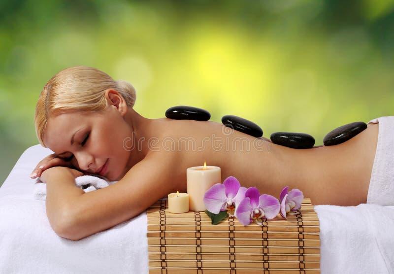 Massage en pierre de station thermale. Femme blonde obtenant le massage chaud de pierres images libres de droits