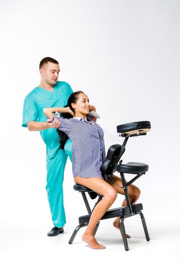 Massage et bureau de thème jeune thérapeute masculin dans le costume bleu faisant le massage arrière avec son genou attaché dans  images libres de droits