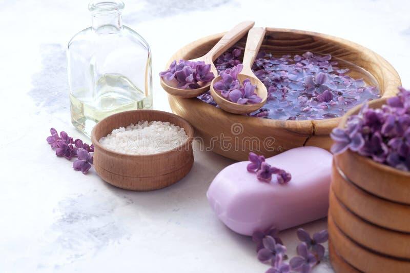 Massage et produits de station thermale avec les fleurs lilas photographie stock libre de droits