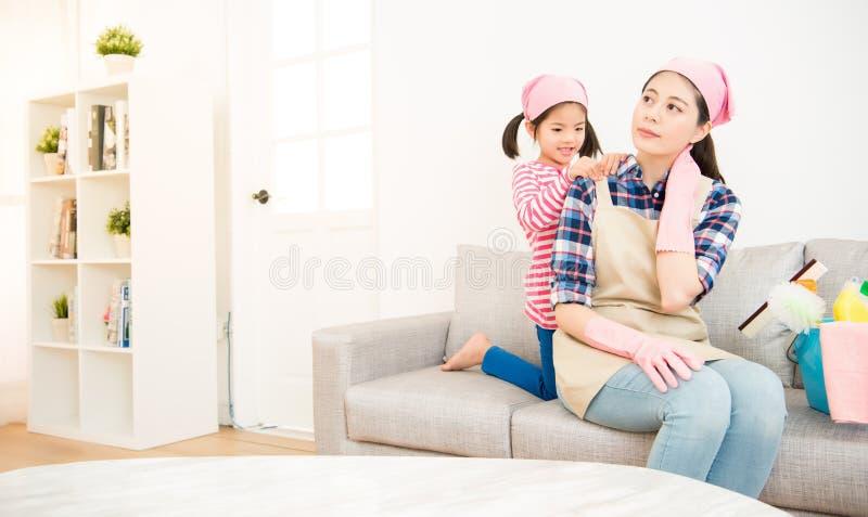 Massage för moder för ungeflicka portion tröttad royaltyfria foton