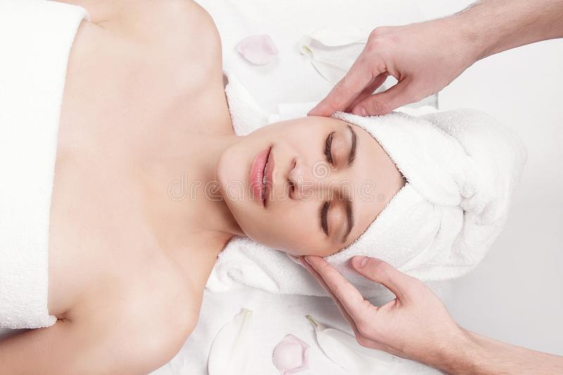Massage for the face and neck of young beautiful woman. In spa salon - close-up portrait stock photo