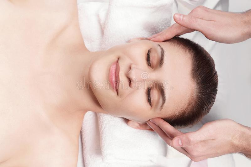 Massage for the face and neck of young beautiful woman. In spa salon - close-up portrait stock images