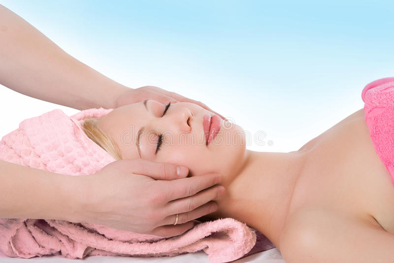 Massage facial de main d'homme à la fille blonde photographie stock