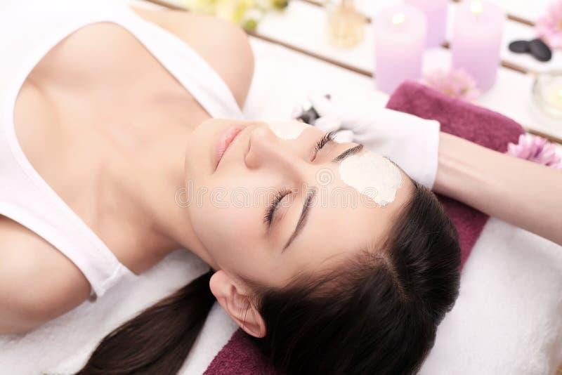 Massage facial de station thermale de cosmétologie Belle brune dans un salon de station thermale photographie stock