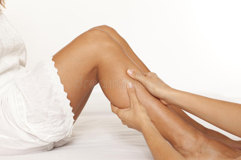 Massage of a female calf muscle. Massage of a women's calf muscle on white background royalty free stock photos