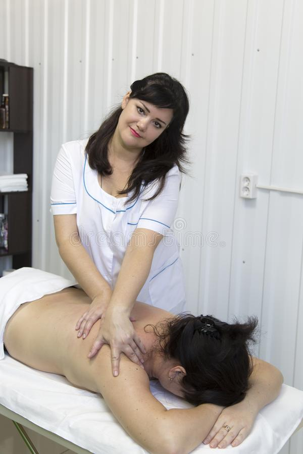 Massage of female shoulders and neck. In a doctor`s office with white walls, a women is given a massage on her neck royalty free stock photos