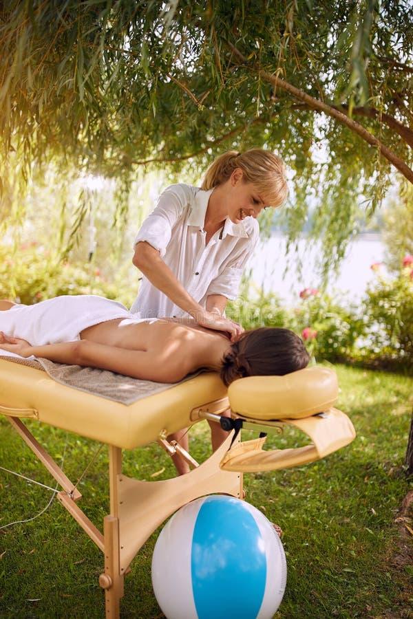 Massage-femme arrière à la station thermale obtenant un massage en nature photos libres de droits
