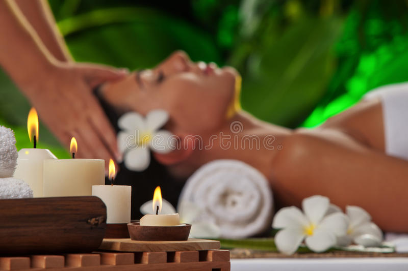 Massage. focused on candles. Portrait of young beautiful woman in spa environment. focused on candles royalty free stock photos