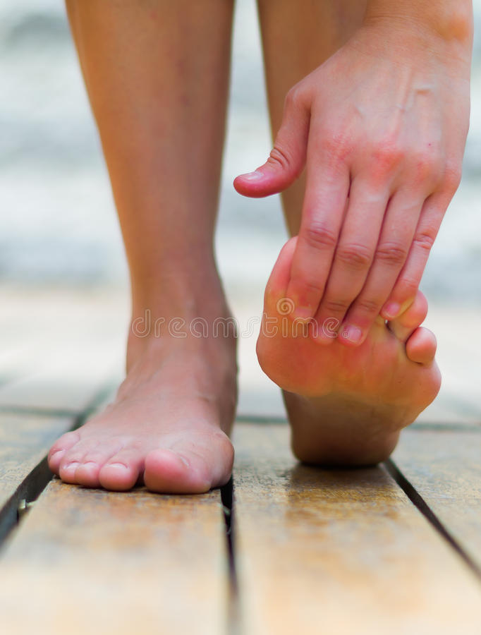 Massage foot when tiptoe hurts, woman making pressure on the fingers, wooden floor.  royalty free stock photography