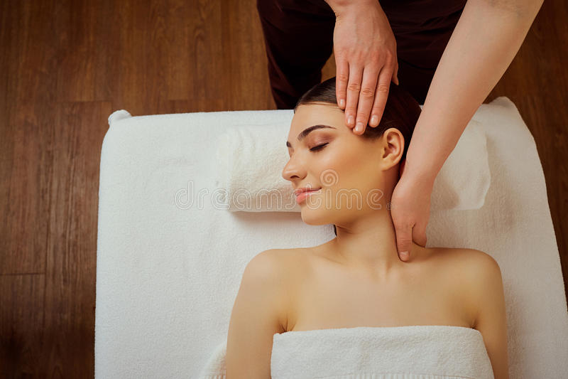 Massage the head of neck to a young woman in massage room royalty free stock images
