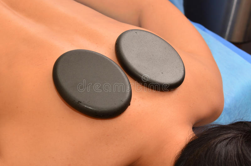 Massage with hot stones stock images