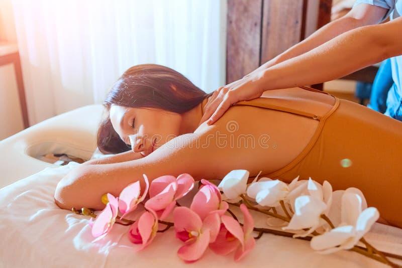 massage kvinna f?r vatten f?r brunnsort f?r h?lsa f?r huvuddelomsorgsfot Behandling f?r Spa kroppmassage Kvinna som har massage i royaltyfri bild