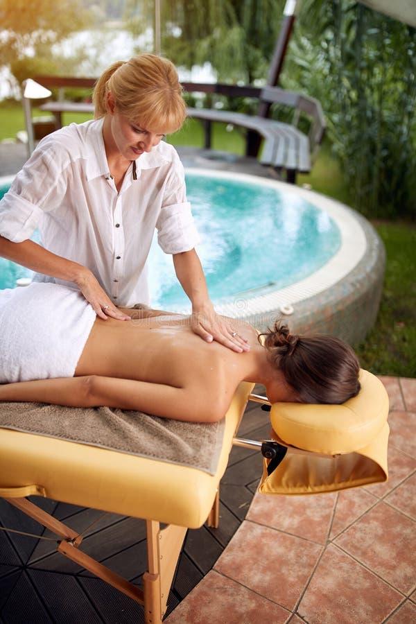 Massage - kvinnlig häleribaksidamassage hemma royaltyfri foto
