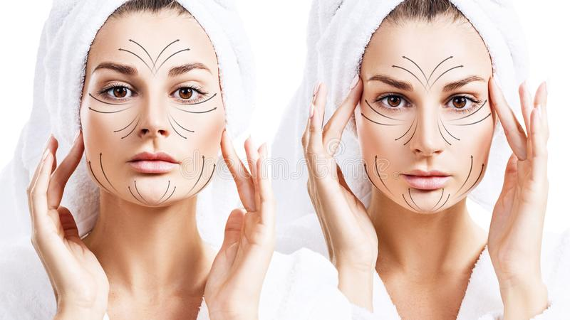 Massage lines on beautiful face of young woman in bathrobe. royalty free stock photography