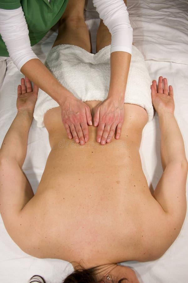 Massage at lumbar region. A natural mature woman having a massage at her lumbar region royalty free stock image