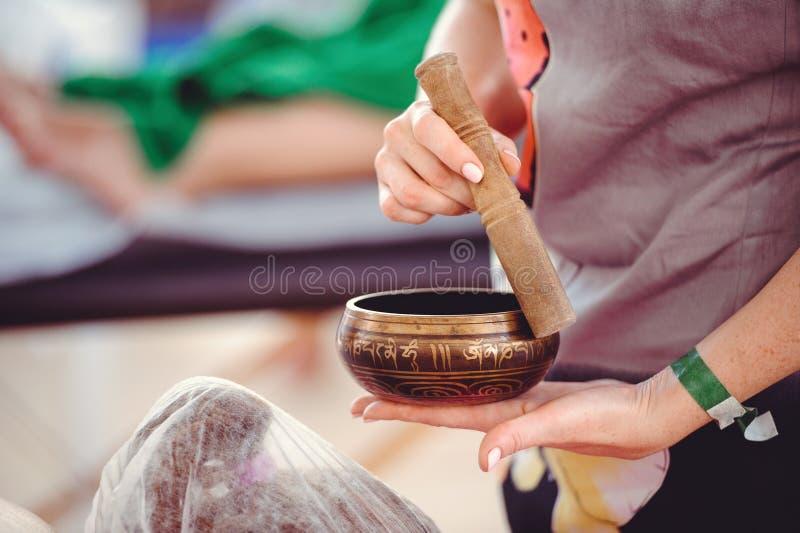Massage med bambupinnar och den tibetana bunken arkivfoton