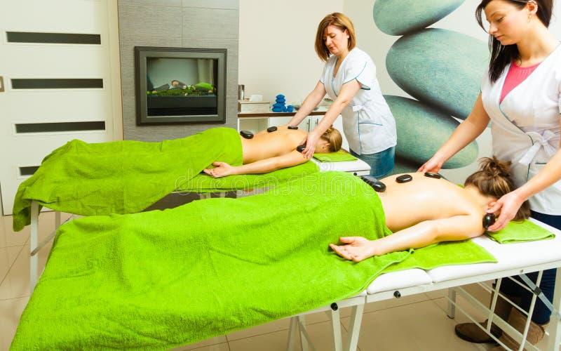 Massage met hete rotsenstenen in schoonheidsspecialist stock afbeelding