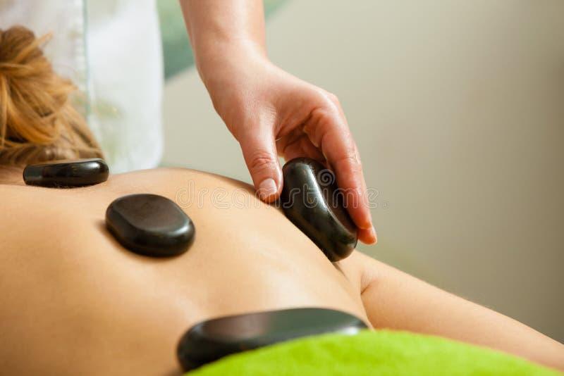 Massage mit heißen Felsensteinen im Kosmetiker lizenzfreie stockbilder