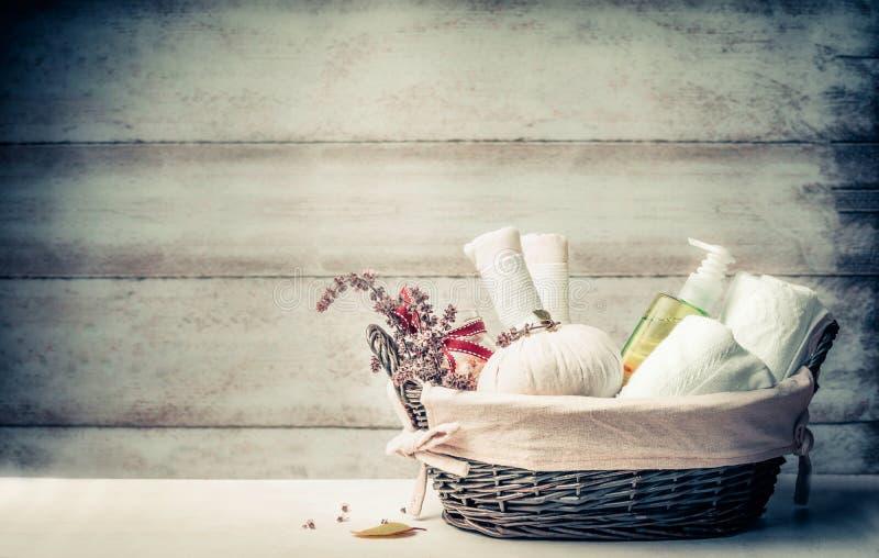 Massage- och bastuinställning med växt- kompressbollar, nya örter och kosmetiska produkter på träbakgrund, främre sikt Sunt arkivfoto