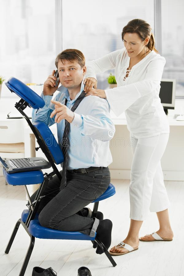 Massage in office. Occupied businessmen talking on mobile, while masseur doing relaxing neck massage royalty free stock photos