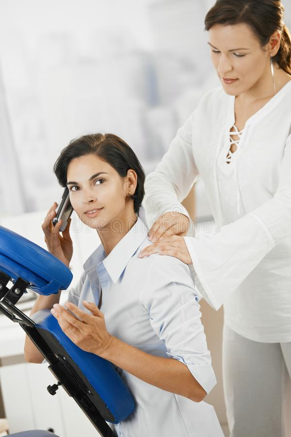 Massage in office. Businesswomen talking on mobile while getting neck massage in office stock photography