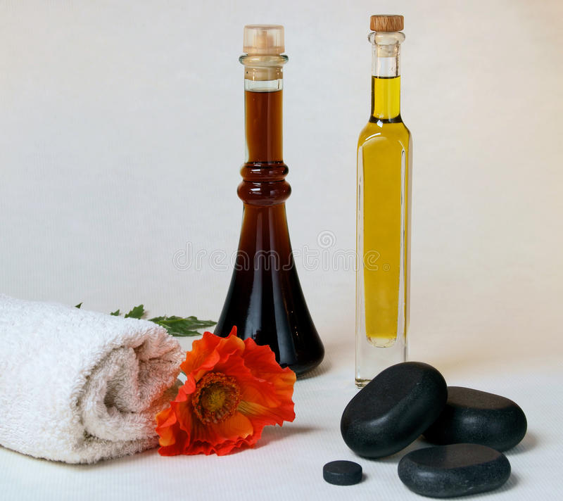 Massage oil with hot stone. Massage oils with hot stone, towel and poppy stock images