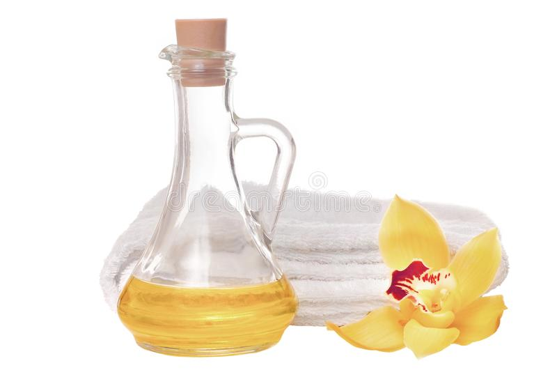 Massage oil. Therapeutic massage composition with orchid flower with towel on white background royalty free stock photography