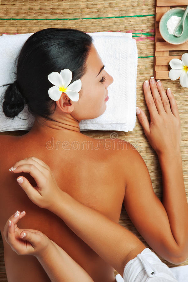On massage. Portrait of young beautiful woman on color back stock photo