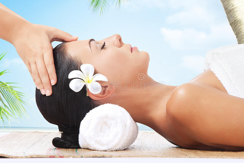 Massage. Portrait of young beautiful woman on color back royalty free stock image
