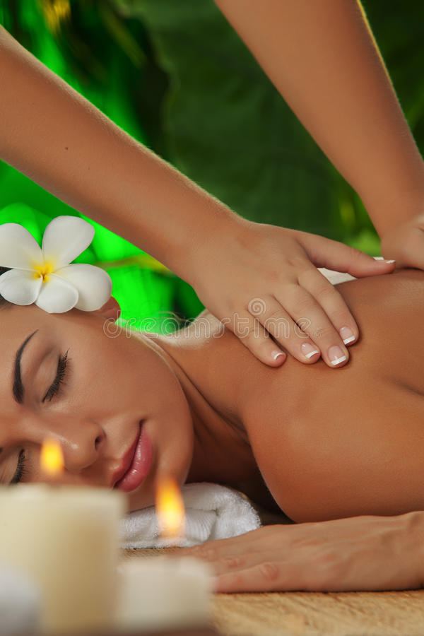 Massage. Portrait of young beautiful woman in spa environment royalty free stock images