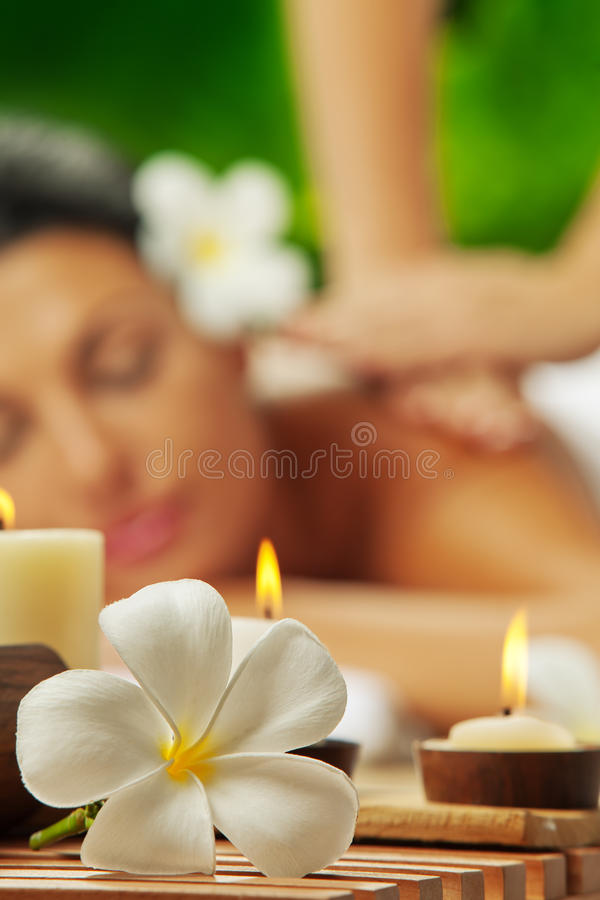 On massage. Portrait of young beautiful woman in spa environment. focused on candles stock photos