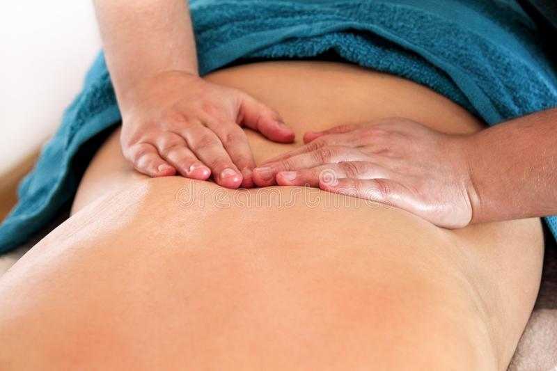 Masseuse hands massaging female back royalty free stock images