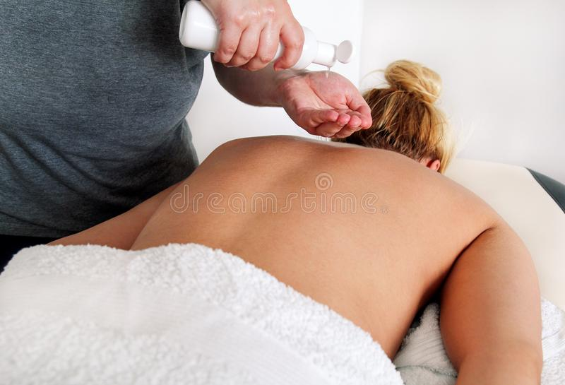 Men hands pump out of a bottle of massage oil. Massage relax studio. Men hands bottle massage oil. Body care. Beautiful women on a massage table is having his stock image