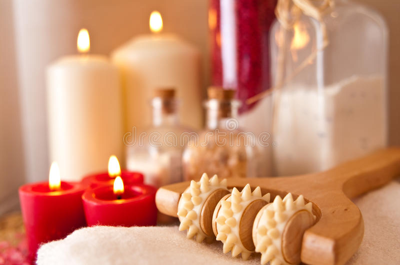 Massage roller and candles. Still life image of a massage roller and lit candles royalty free stock photos