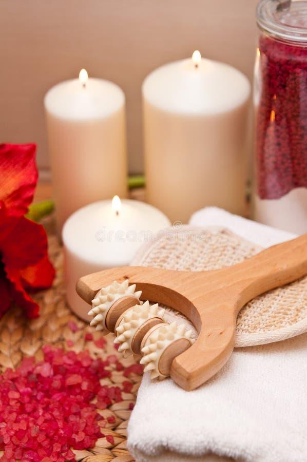 Massage Roller, Candles and Bath Salts. Spa still life of wooden massage roller, lit candles and pink crystal bath salts stock photo
