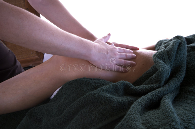 Massage by the sea. Woman middle age relaxing with professional massage at resort by the sea stock photography