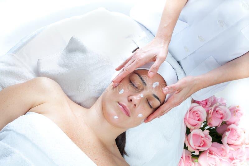 Massage spa. Facial treatment. Close-up of a female receiving facial massage at spa salon royalty free stock image