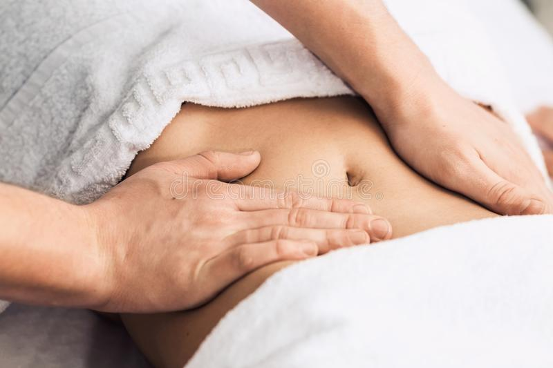 Massage of the stomach in the spa. Cosmetic clinic, spa, wellness center, healthcare concept royalty free stock photography