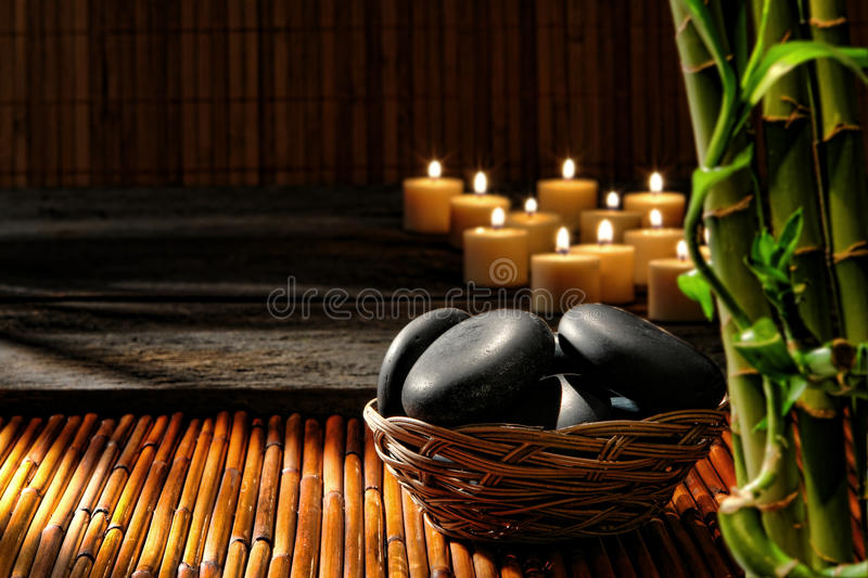 Massage Stones in Basket in Wellness Holistic Spa. Smooth polished black hot massage stones in a basket with candles burning and bamboo stems decor in the royalty free stock photography