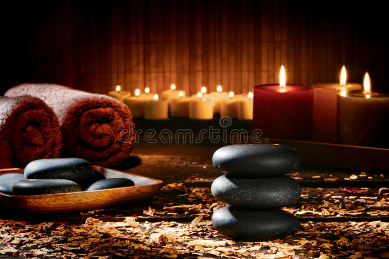 Massage Stones Cairn in a Wellness Holistic Spa. Hot massage black polished stones Zen style cairn and treatment stone tray with soft towels and glowing royalty free stock images