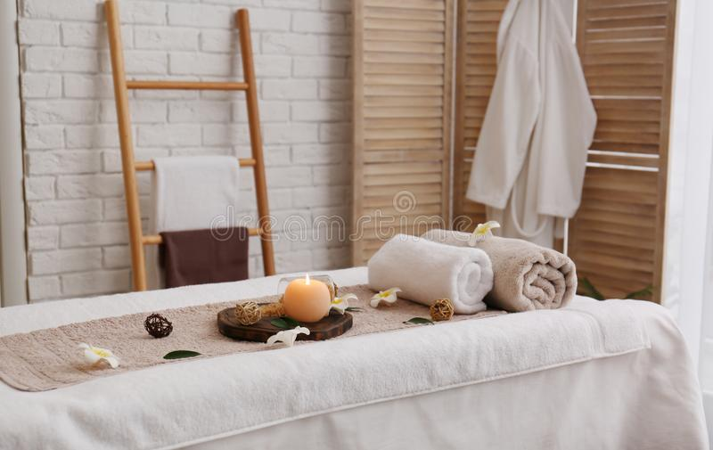 Massage table with towels, candle and sea salt in spa salon stock photos
