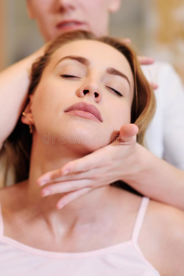 The massage therapist does a neck massage. To a pretty pregnant girl royalty free stock images