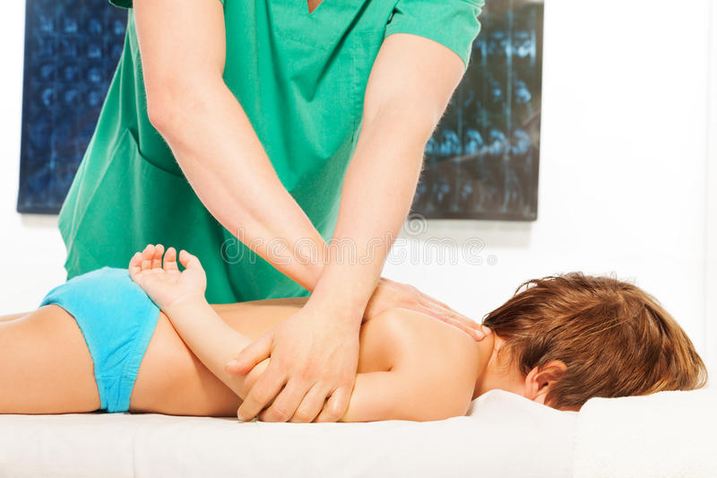Massage therapist doing exercises with little boy stock image