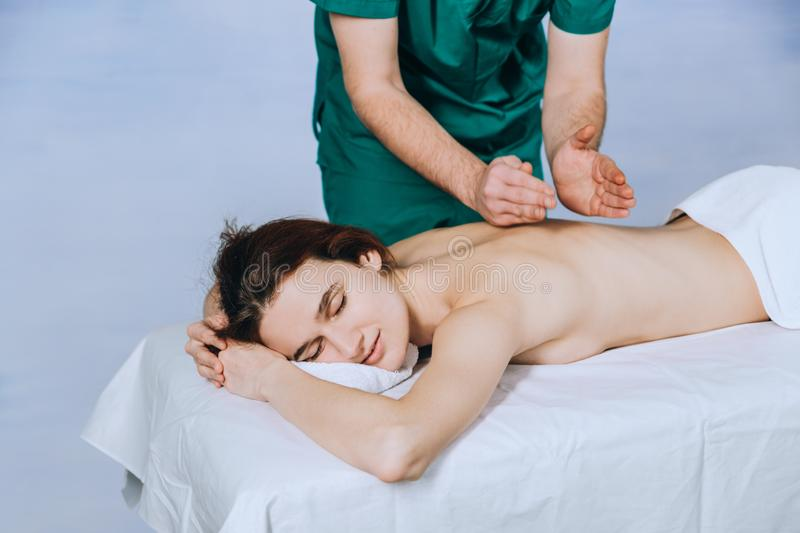 Massage therapist doing massotherapy of a young woman. Beautiful relaxed face of a young woman with brown hair and closed eyes royalty free stock photos