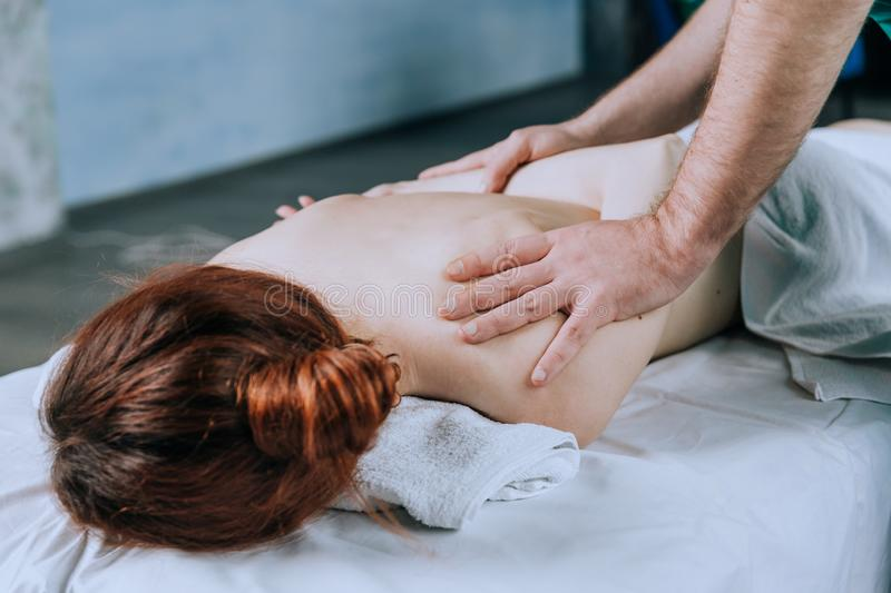 Massage therapist doing massotherapy of a young woman, elbow joint massage. Beautiful relaxed  young woman. With brown hair royalty free stock image