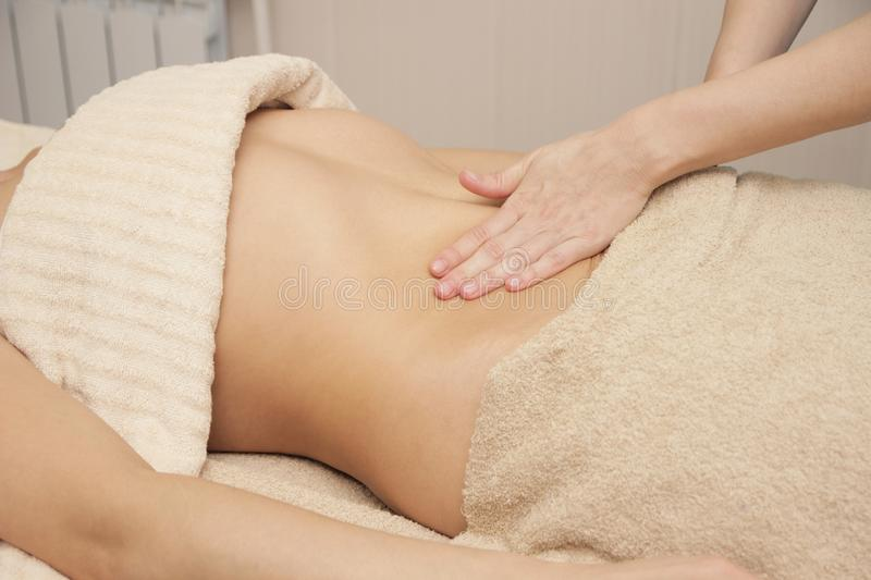 Massage therapist doing a thermic massage for the abdomen for a woman stock photos