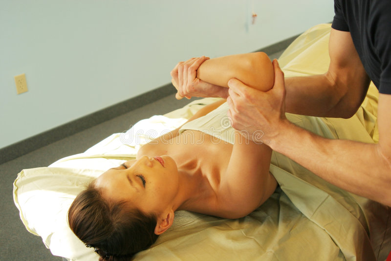 Massage therapist giving massage to woman royalty free stock photos